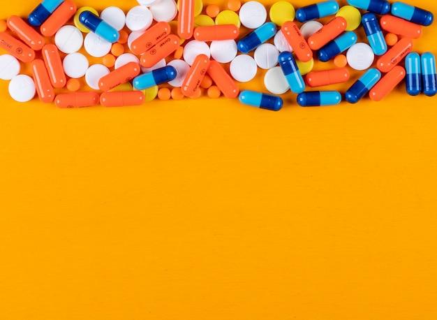 オレンジ色の表面にカラフルな錠剤
