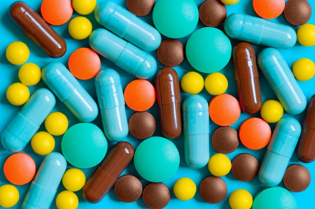 Colorful pills scattered on the blue background