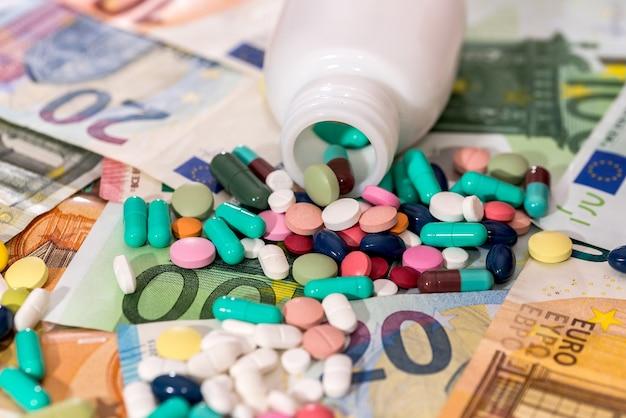 ユーロ紙幣のクローズアップのコンテナとカラフルな錠剤