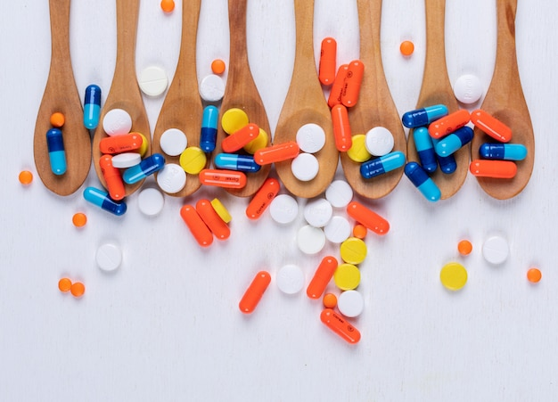 Colorful pills in wooden spoons