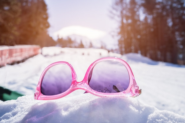 Colorful of pink sunglasses placed on snow at sport ski resort valley with pine in winter time
