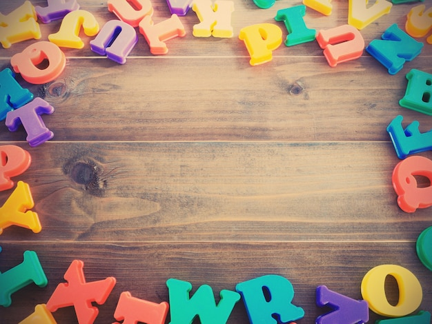 Colorful plastic alphabets on wooden table background, vintage filter effect.