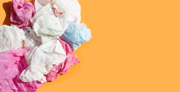 Colorful plastic bags on orange surface