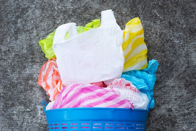 Colorful plastic bags with trash basket on cement floor.