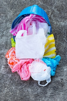 Colorful plastic bags with trash basket on cement floor