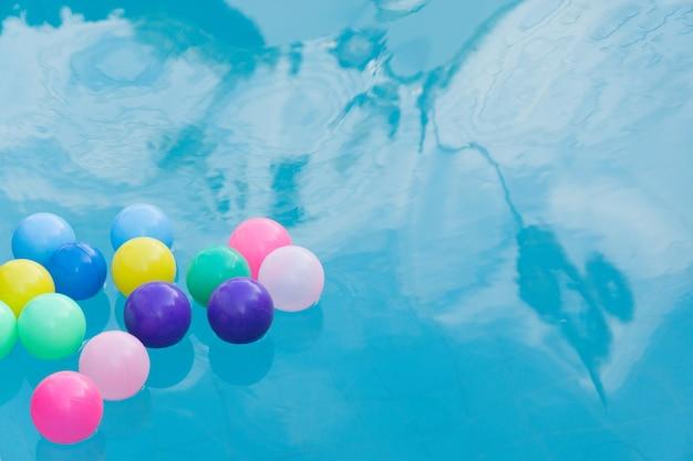 スイミングプールでカラフルなプラスチックボール