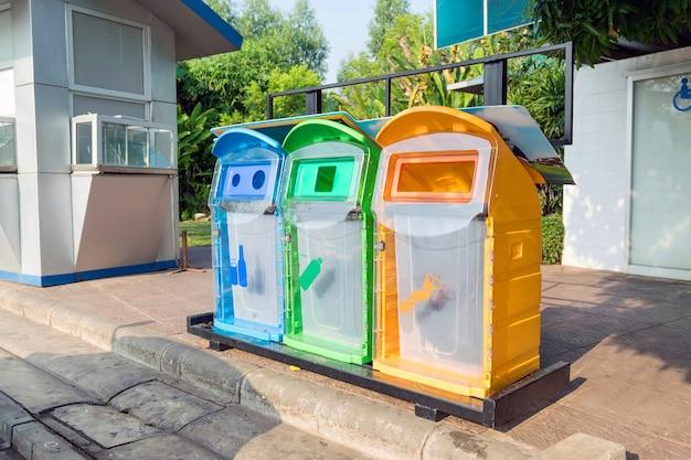 公園内のさまざまな種類の廃棄物用のカラフルなプラスチック製のゴミ箱。