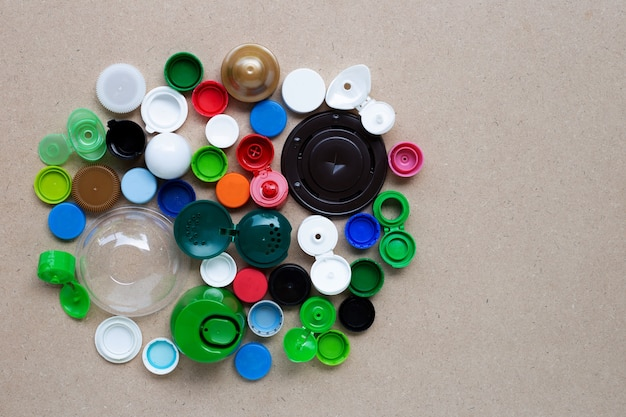 합판 배경에 다채로운 플라스틱 병 뚜껑과 플라스틱 유리 뚜껑. 평면도
