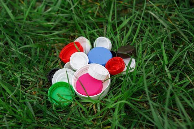 푸른 잔디에 다채로운 플라스틱 병 뚜껑