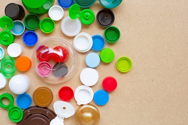 Colorful plastic bottle caps and plastic glass lid on plywood