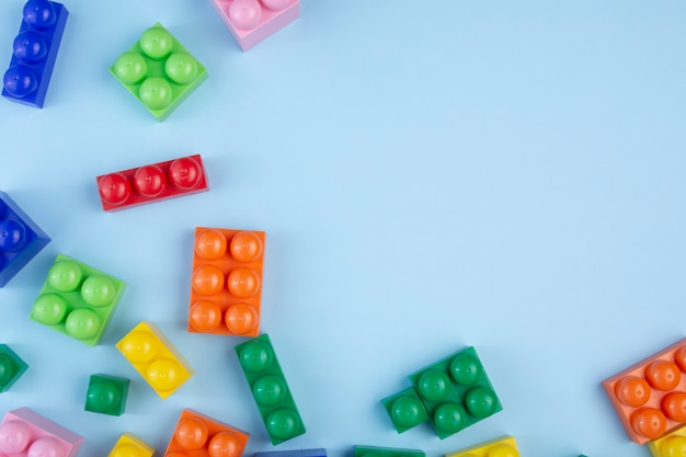 Colorful plastic building blocks on blue background. copy space for text. flat lay.