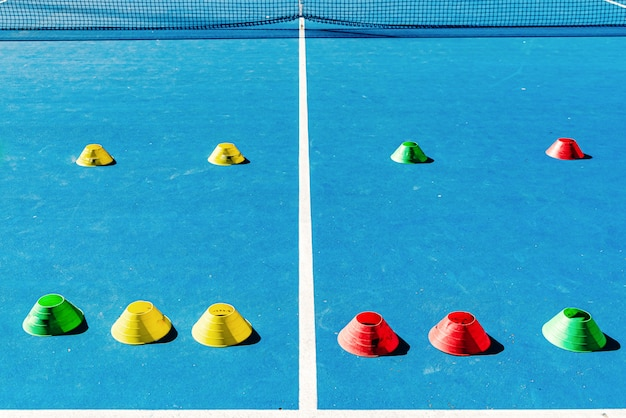 Colorful plastic cones on a blue cement tennis court with white lines