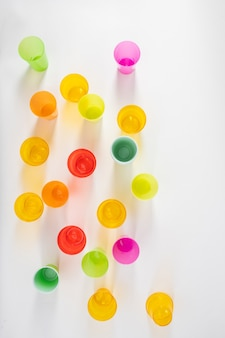 カラフルなプラスチック製のコップ。スタジオでの写真撮影中に一列に立っている有害な使い捨てプラスチックカップ