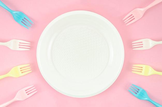 Разноцветные пластиковые тарелки на розовом фоне