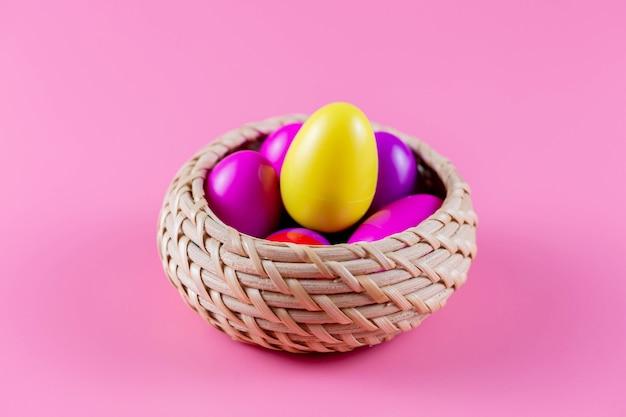 ピンクの背景の籐のバスケットにカラフルなプラスチックのイースターエッグ。