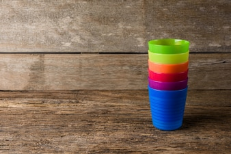 Colorful plastic glass on wooden background