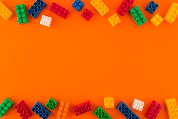 オレンジ色の背景にカラフルなプラスチックレゴ