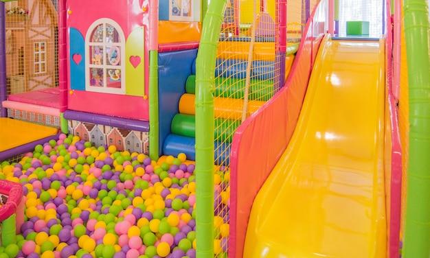 놀이터에 메쉬와 다채로운 공이 있는 다채로운 플라스틱 슬라이드, 실내 놀이터에서 어린이 안전.