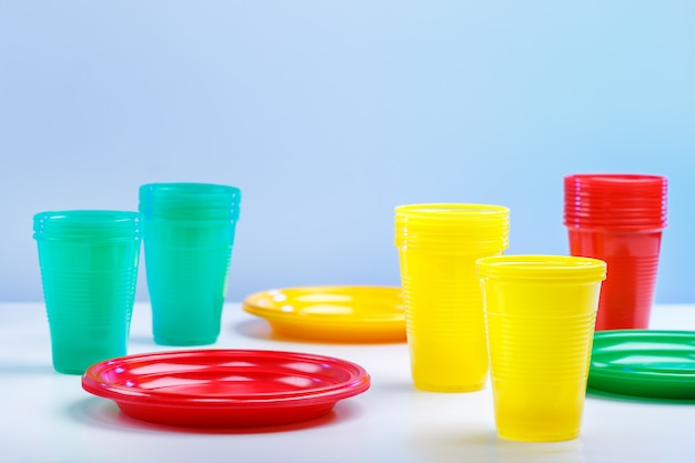 Colorful plastic tableware on blue background with copy space.