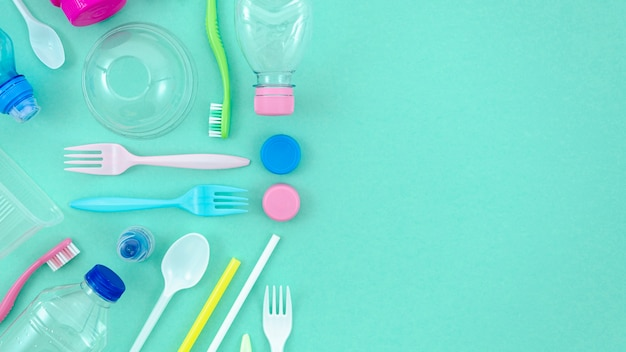 Colorful plastic tableware on turquoise background