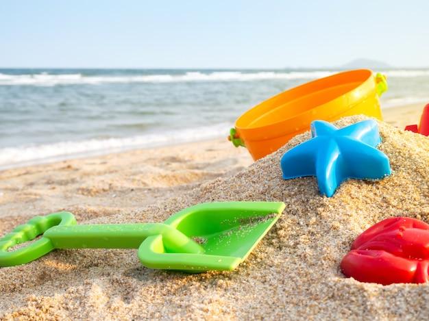 砂の上のカラフルなプラスチックのおもちゃ
