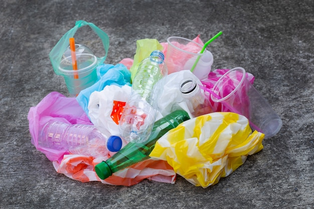 Colorful plastic waste, bags, cups, bottles, straws on cement