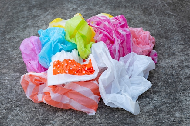 Colorful plastic waste on cement floor background.