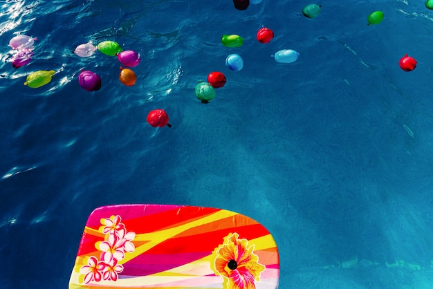 Colorful plastic water balloons floating in a pool to play on vacation to cool off.