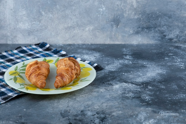 A colorful plate of fresh croissants placed on a marble table.