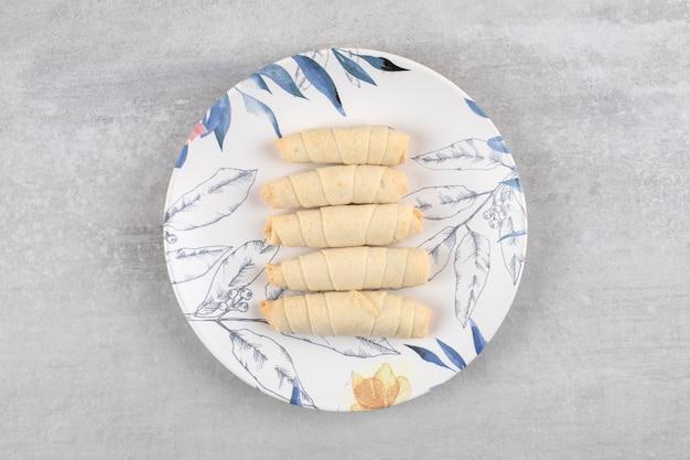 Piatto colorato di mutaki dolci fatti in casa sul tavolo di pietra.