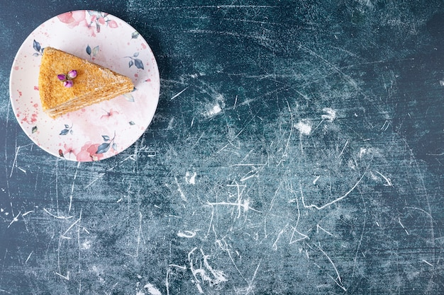Красочная тарелка сладкого медового торта на мраморном фоне.