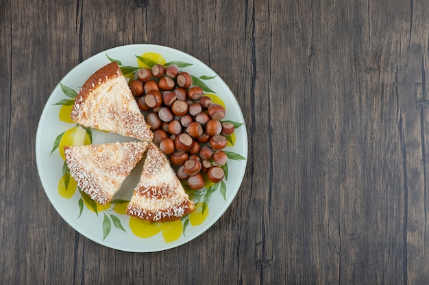A colorful plate with pieces of delicious pie and sweet chestnuts .