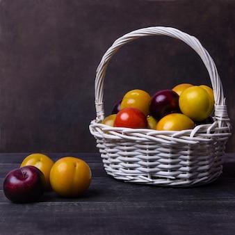 Красочные сливы фрукты в корзине на черном пространстве изолированы