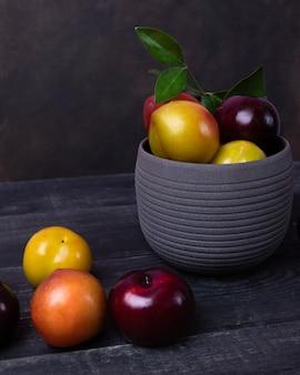 Красочные плоды сливы в горшке и тарелке на черном пространстве изолированы