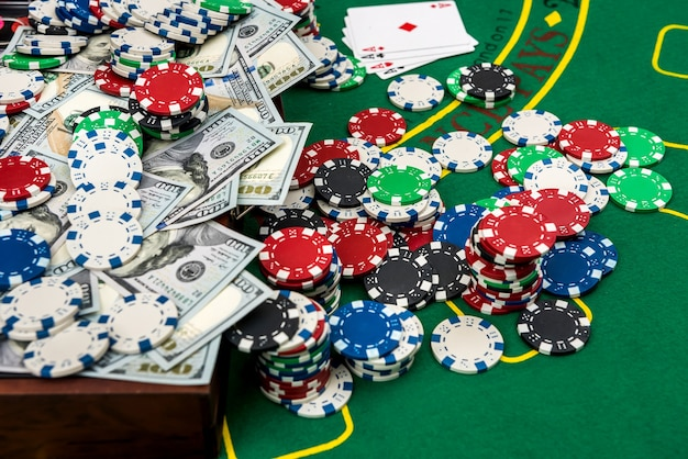 Colorful poker chips with american dollars in wooden box on green playing table.