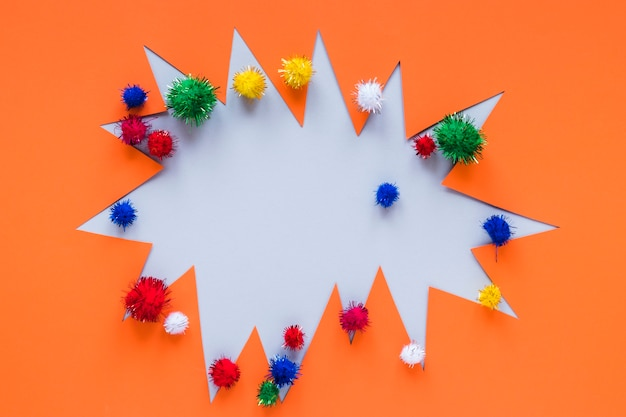 Colorful pom-poms with carnival paper cut-out