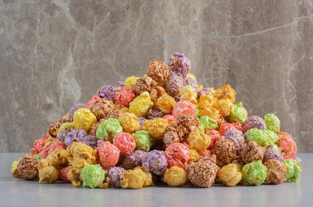 Caramelle colorate popcorn ammucchiate sulla superficie di marmo