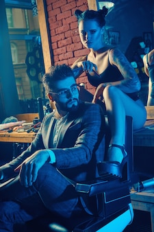 Colorful portrait of beautiful couple: brutal man in elegant suit and sexy girl with a tattoo wearing lingerie in barbershop