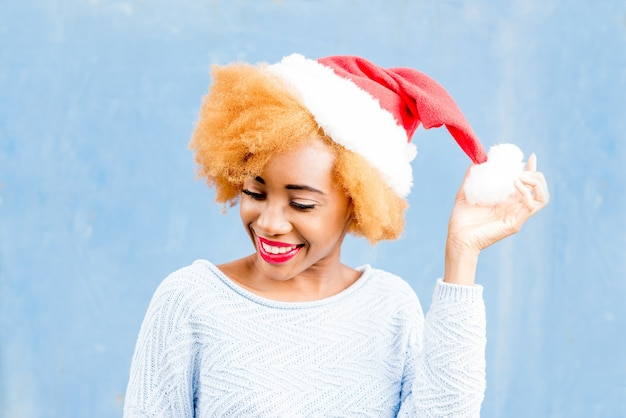 Colorful portrait of a cute african woman in christmas hat on the blue wall background. winter holidays concept