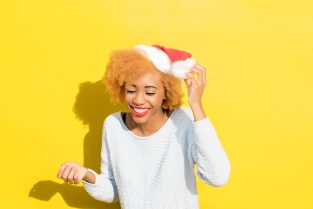 Colorful portrait of a cute african woman in christmas hat on the yellow background. winter holidays concept