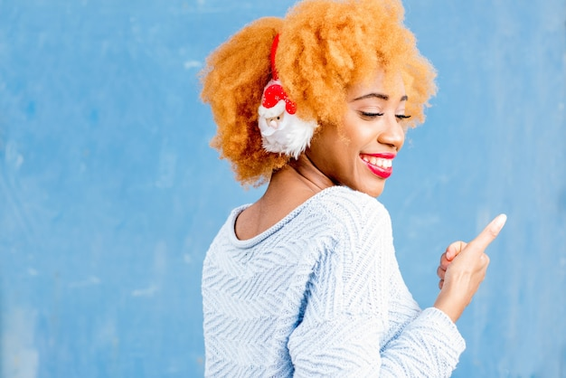Colorful portrait of a cute african woman in santa claus headphones on the blue wall background. winter holidays concept