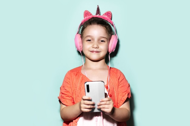 Colorful portrait of happy confident little child girl, holding smartphone and listening the music with headphones on studio background of cyan, aqua menthe color.
