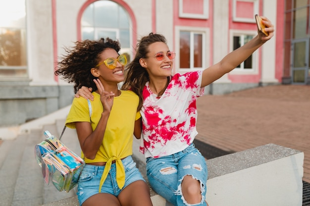 Colorful portrait of happy young girls friends smiling sitting in street taking selfie photo on mobile phone, women having fun together