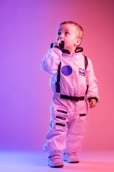 Colorful portrait of a little boy wearing american astronaut clothes, illuminated with red and blue light. astronaut and children concept.