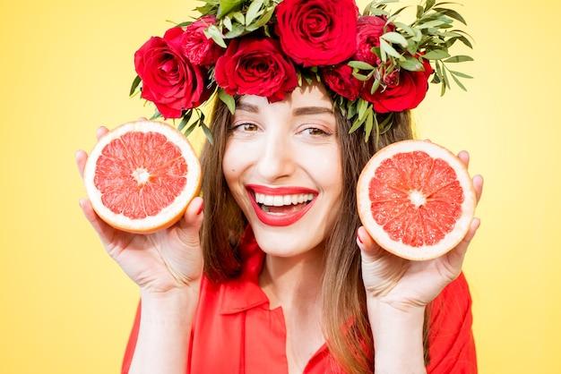 Красочный портрет красивой женщины с цветочным венком, держащей дольки грейпфрута на желтом фоне