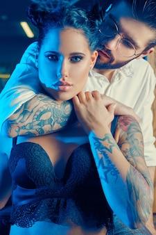 美しいカップルのカラフルな肖像画:エレガントなスーツの残忍な男と理髪店でランジェリーを身に着けている入れ墨を持つセクシーな女の子