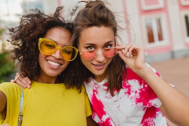 휴대 전화에 셀카 사진을 찍는 거리에 앉아 웃고 행복 한 젊은 여자 친구의 화려한 초상화, 여성이 함께 재미