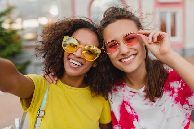 携帯電話でselfie写真を撮って、一緒に楽しんでいる女性、通りに座って笑っている幸せな若い女の子の友人のカラフルな肖像画