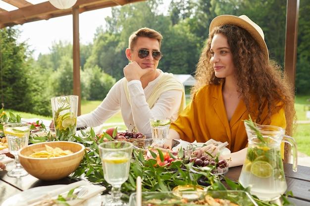 屋外の夏のパーティー中にテーブルに座って友人と夕食を楽しんでいる若いカップルのカラフルな肖像画