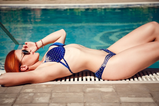 Colorful portrait of pretty young woman in blue swimsuit